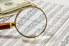 Money. Looking through magnifying glass to the dollars banknotes and financial report Stock Photography
