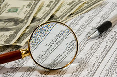 Money. Looking through magnifying glass to the dollars banknotes and financial report Royalty Free Stock Photos