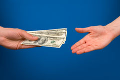 Money. One hand gives money in other hand over blue background Stock Images