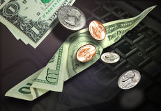 Money. Dollar bills and coins suspended in air and a laptop in background Royalty Free Stock Image