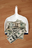 Money. Dollars and dustpan royalty free stock image