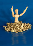 In The Money. Mannequin surrounded by gold nuggets.  Metaphor Royalty Free Stock Photo