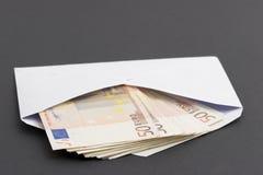 Money. In envelope on dark background Stock Photos