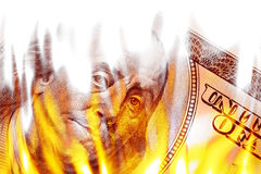 Money Ablaze in Flames. Burning American money with Benjamin Franklin's face appearing on fire on a one hundred dollar bill Stock Images