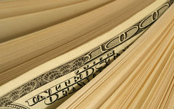 Money abstract. Close-up of one hundred dollars bill between a stack of bills Royalty Free Stock Photography