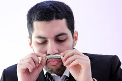 Money addiction. Image of arab business man wearing black suit and smelling money as money addiction Stock Photos