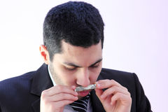 Money addiction. Image of arab business man wearing black suit and smelling money as money addiction Royalty Free Stock Image