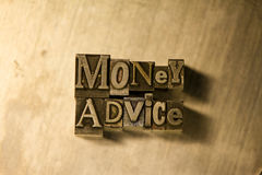 Money advice - Metal letterpress lettering sign. Lead metal 'Money advice' typography text on wooden background Royalty Free Stock Image