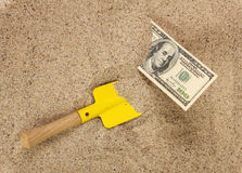Money american hunderd dollar bills in sand and yellow shovel Stock Photos