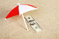 Money american hundred dollar bill unter sunshade on beach sand Stock Images