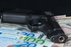 Money as a backdrop and a gun Royalty Free Stock Photography