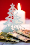 Money as christmas present. Christmas tree with burning candle and money on red background Royalty Free Stock Photo
