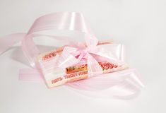 Money as a gift. Gift money is decorated with pink ribbon Royalty Free Stock Photo