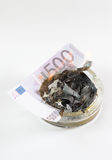 Money in an ashtray burns Stock Photo
