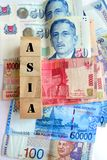 Money in asian currencies. A conceptual photograph showing some cash bank notes in various different asia country currency, spread out to form a colorful Royalty Free Stock Photos