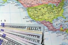 Money atop an old atlas Stock Photo