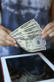 Money on the background of the tablet Royalty Free Stock Image