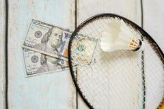 Money and badminton shuttlecocks. On wooden background Stock Image