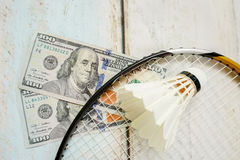 Money and badminton shuttlecocks. On wooden background Royalty Free Stock Images
