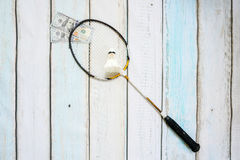 Money and badminton shuttlecocks. On wooden background Stock Images