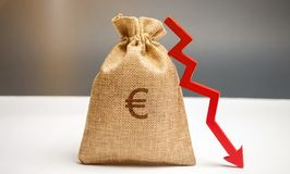 Money bag with a euro sign and an arrow down. The concept of reducing profits. Drop in revenue. Low salary. Financial and economic royalty free stock photo
