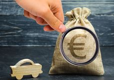 Money bag with Euro sign and miniature car. The concept of saving money to buy a car. Auto insurance. Saving. Loan repayment. Amortization. Buy a vehicle royalty free stock photos