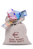 Money bag full of Euros. Photo of a money bag full and overflowing Euro banknotes, cut out on a white background stock photography