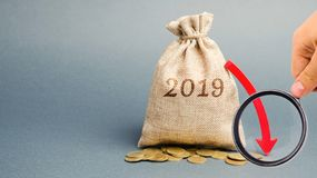 Money bag with the inscription 2019 and the red arrow down. Annual report. Business recession. Unreliable investment. Crisis and. Bankruptcy. Drop in profits stock photos