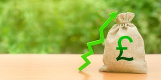Money bag with pound sterling symbol and green up arrow. The growth of the national economy and the strength of the exchange rate
