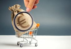 Money bag in supermarket trolley and euro sign. Cashback. Money Management. Money market. Sale, discounts and low prices. Gift stock photos