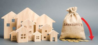 A money bag with the word Bankruptcy, a down arrow and wooden houses. Bankruptcy auction. Mortgaged property. Financial collapse. stock image