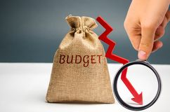 Money bag with word Budget and down arrow. Unsuccessful business and poverty. Profit decline. Loss of investment. Low wages and. Savings. Economic crisis. fall royalty free stock image