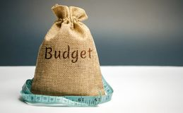 Money bag with the word Budget and tape measure. The concept of limited profit. Lack of money and poverty. Small income. Salary. Reduction. Unsuccessful royalty free stock photo