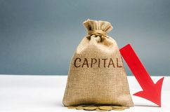 Money bag with the word Capital and arrow to down. Capital outflow. Currency devaluation. Falling stock quotes. Financial and stock photo