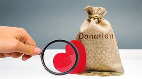 A money bag with the word Donation and a red heart. Accumulation of money for a medical donation. Health care. Saving. Social stock photo