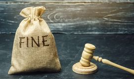 Money bag with the word Fine and the judge`s hammer. Penalty as a punishment for a crime and offense. Financial punishment. Violations of traffic laws. Fraud royalty free stock photography