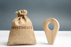 Money bag with the word Investments and a geolocation marker. Point and direct investments in a region or country. Construction of. New factories and stock images