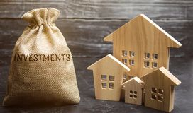 Money bag with the word Investments and wooden houses. The concept of attracting investment in real estate. Search for investors. For construction. Investment royalty free stock photography