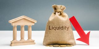Money bag with the word Liquidity, down arrow and bank building. The concept of market decline. Drop in sales. Crisis and collapse. Failure to quickly sell stock photos