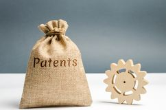 Money bag with the word Patents and a wooden gear. Registration of patents and copyright compliance. Licensing technology and. Scientific discoveries. Purchase royalty free stock photography