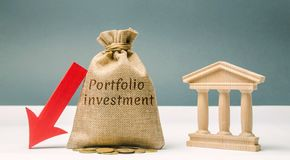 Money bag with the word Portfolio Investment and a down arrow near the bank. The outflow of deposits. The fall of the bank`s royalty free stock photo
