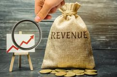 Money bag with the word Revenue and graph up. The concept of increasing profits and finance. Budget growth in the company. The royalty free stock photography
