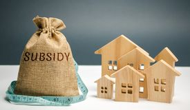 Money bag with the word Subsidy and wooden houses. Financial aid, support to the population. Cash grants, interest-free loans. Tax