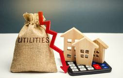Money bag with the word Utilities and an arrow down and wooden houses on the calculator. Reduced prices for utilities. Low prices royalty free stock photography