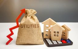 Money bag with the word Utilities and an up arrow and houses on a calculator. The concept of raising prices for the use of. Utilities. Payment of bills. Rising stock images
