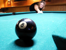 Money ball. Woman out of focus shooting cue ball with focus on 8-ball, shallow depth of field stock images