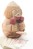 Money Bank and Banknotes. A hand carved wooden monkey bank holding maracas with banknotes Royalty Free Stock Photos