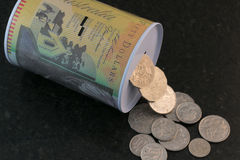 Money Bank. Money pouring out of an Australian 50 Dollar money bank Stock Image