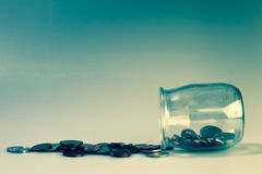 Money and banking concept with coins and jar. Blue background Royalty Free Stock Photography
