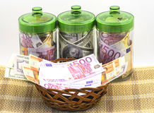 Money in banks. Bills euro and dollars in glass banks and basket with bill on foregrounds is insulated on white background Stock Photos